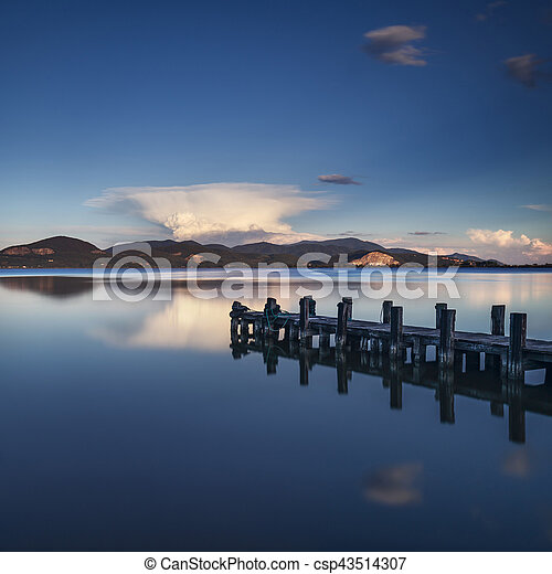 Wooden pier or jetty on a blue lake sunset and sky reflection on water. Versilia Tuscany, Italy - csp43514307