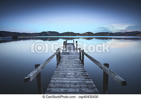 Wooden pier or jetty on a blue lake sunset and sky reflection on water. Versilia Tuscany, Italy - csp40435430