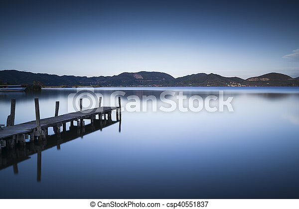 Wooden pier or jetty on a blue lake sunset and sky reflection on water. Versilia Tuscany, Italy - csp40551837