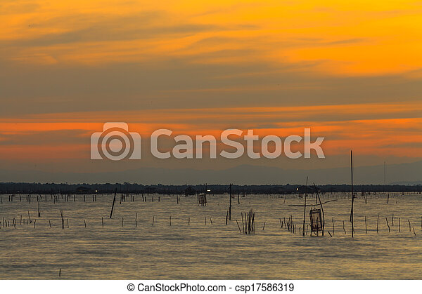 Wooden pier or jetty remains on a blue lake sunset and cloudy sky reflection on water. - csp17586319