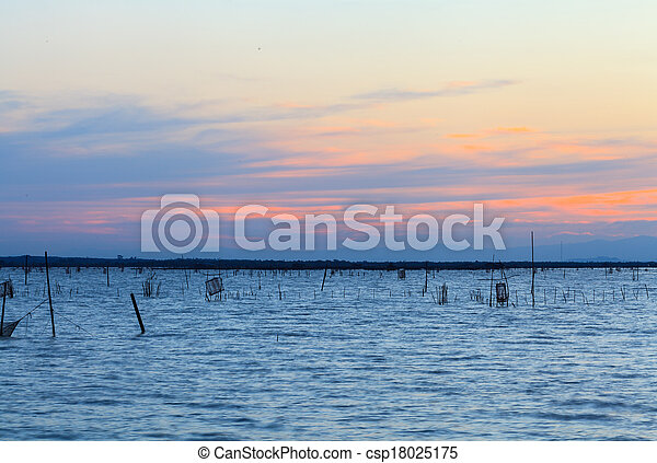 Wooden pier or jetty remains on a blue lake sunset and cloudy sky reflection on water. - csp18025175