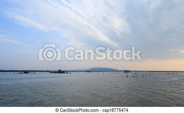 Wooden pier or jetty remains on a blue lake sunset and cloudy sky reflection on water. - csp18775474