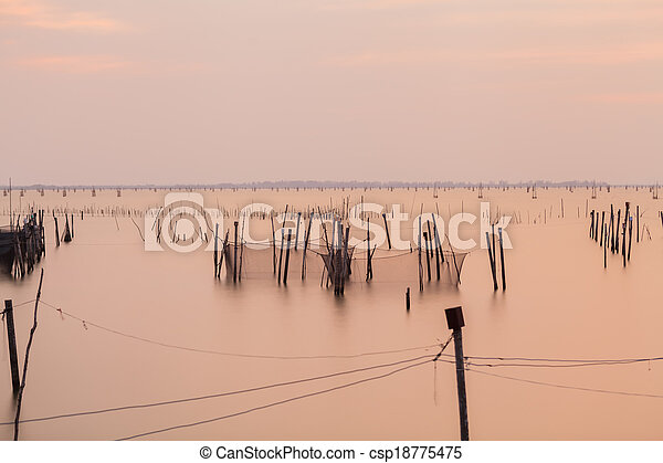 Wooden pier or jetty remains on a blue lake sunset and cloudy sky reflection on water. - csp18775475