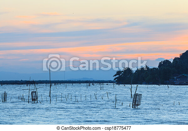 Wooden pier or jetty remains on a blue lake sunset and cloudy sky reflection on water. - csp18775477