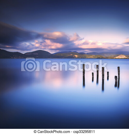 Wooden pier or jetty remains on a blue lake sunset and sky reflection on water. Versilia Tuscany, Italy - csp33295811
