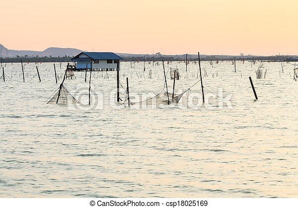 Wooden pier or jetty remains on a blue lake sunset and cloudy sky reflection on water. - csp18025169