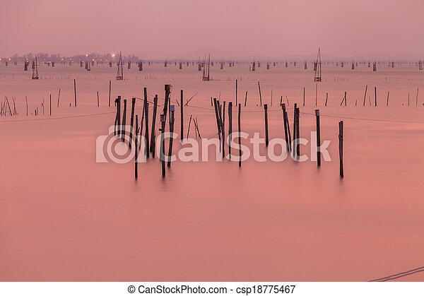 Wooden pier or jetty remains on a blue lake sunset and cloudy sky reflection on water. - csp18775467