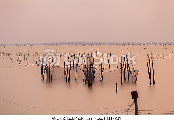 Wooden pier or jetty remains on a blue lake sunset and cloudy sky reflection on water. - csp18847261