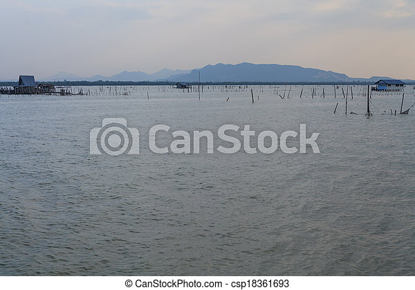 Wooden pier or jetty remains on a blue lake sunset and cloudy sky reflection on water. - csp18361693