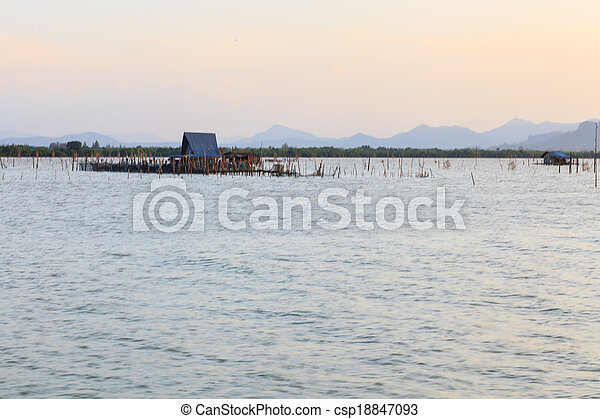 Wooden pier or jetty remains on a blue lake sunset and cloudy sky reflection on water. - csp18847093