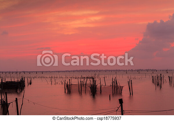 Wooden pier or jetty remains on a blue lake sunset and cloudy sky reflection on water. - csp18775937