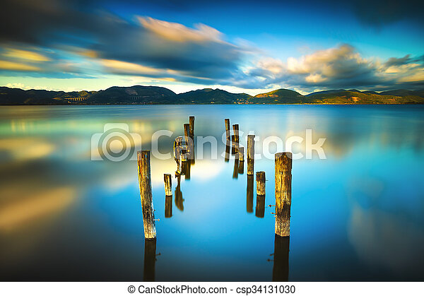 Wooden pier or jetty remains on a blue lake sunset and sky reflection on water. Versilia Tuscany, Italy - csp34131030