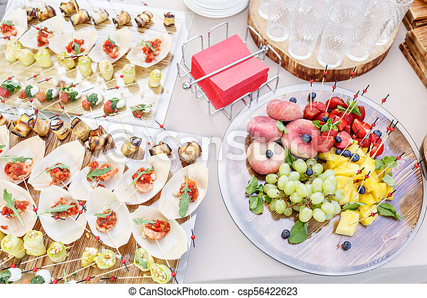 Wooden plate with sliced fruits and berries on a buffet table. and other snacks and canapes. Summer party outdoor. Horizontal photo - csp56422623