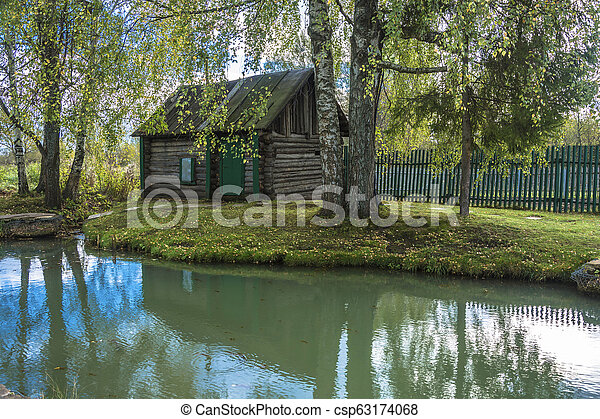 Wooden Russian bathhouse on the shore of a small pond in the village of Vyatskoye, Russia. - csp63174068