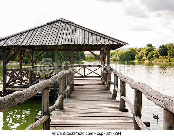 Wooden shelter on a quiet lake - csp78217294