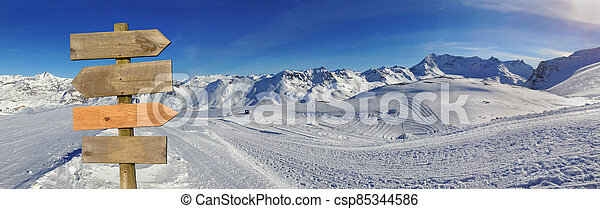 wooden sign in front of a beautiful snowy mountain landscape in winter under blue sky - csp85344586