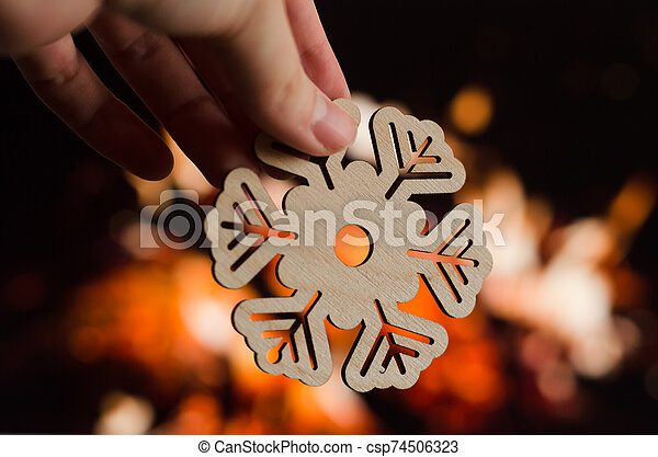 Wooden snowflake christmas decoration on fireplace background - csp74506323