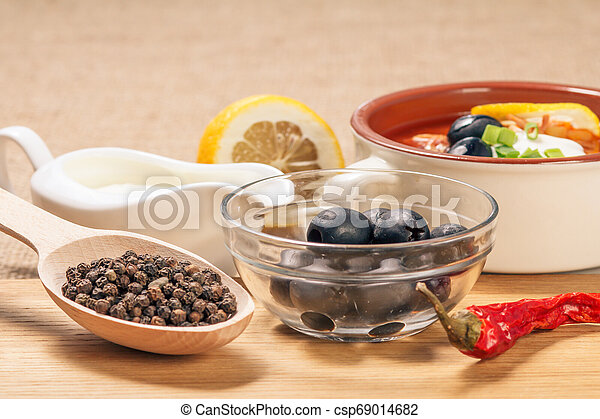 Wooden spoon with black peppercorn, bowl with olives, dried red pepper on cutting board and ceramic soup bowl with saltwort, sauceboat and cut lemon. - csp69014682