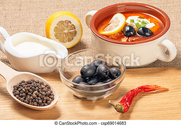 Wooden spoon with black peppercorn, bowl with olives, dried red pepper on cutting board and ceramic soup bowl with saltwort, sauceboat and cut lemon. - csp69014683