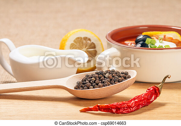 Wooden spoon with black peppercorn, dried red pepper on cutting board and ceramic soup bowl with saltwort, sauceboat and cut lemon. - csp69014663