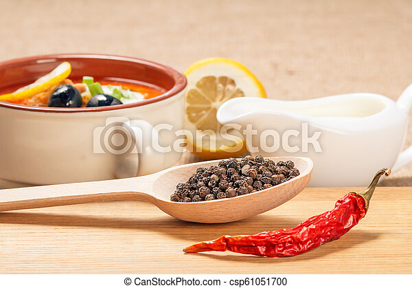 Wooden spoon with black peppercorn, dried red pepper and bowl with saltwort - csp61051700