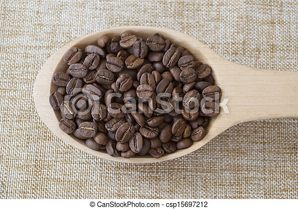 Wooden spoon with coffee beans on sackcloth. - csp15697212