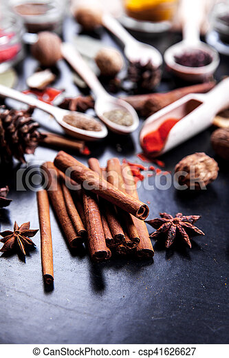wooden spoons with spices on black background - csp41626627