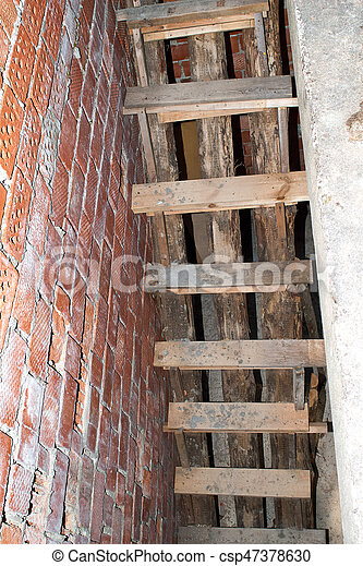 Wooden staircase in brick building under construction