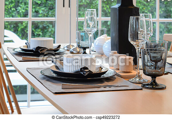 wooden table and chairs in dining room with elegant table setting - csp49223272