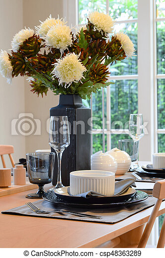 wooden table in dining room with elegant table setting - csp48363289