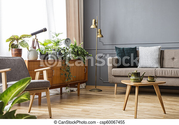Wooden table in vintage living room interior with cabinet between sofa and armchair. Real photo - csp60067455