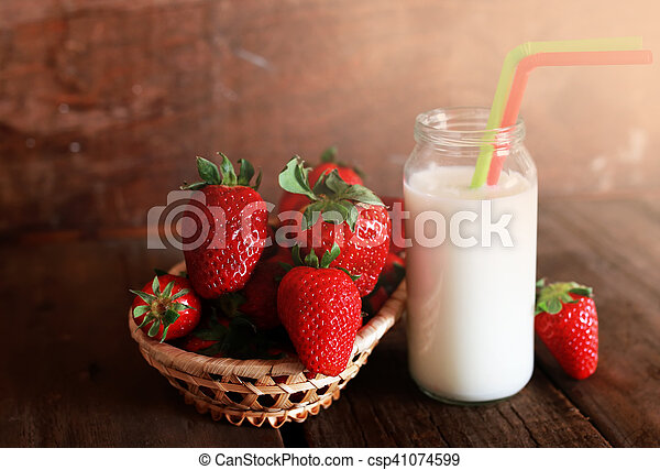 wooden table with strawberries and milk in a glass - csp41074599