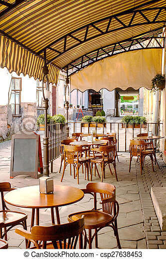 wooden tables and chairs under a canopy near the old cafe - csp27638453