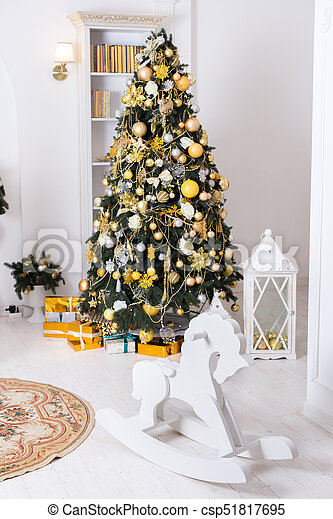 Wooden toy horse, giftboxes, golden christmas decorations balls hanging on a decorative christmas tree. - csp51817695