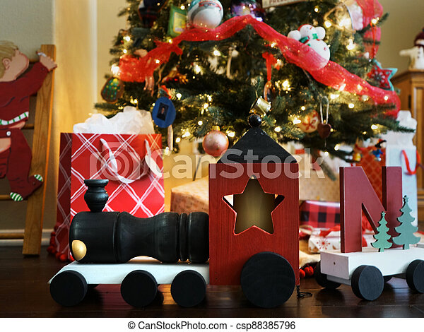 Wooden train and gifts under a Christmas Tree - csp88385796