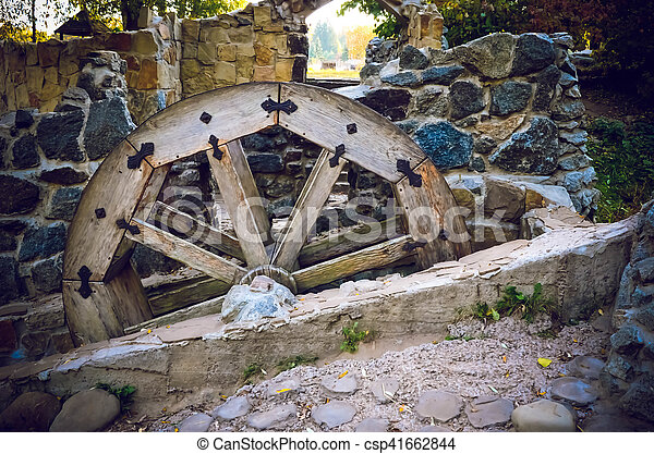 Wooden wheel of an old watermill on the river - csp41662844