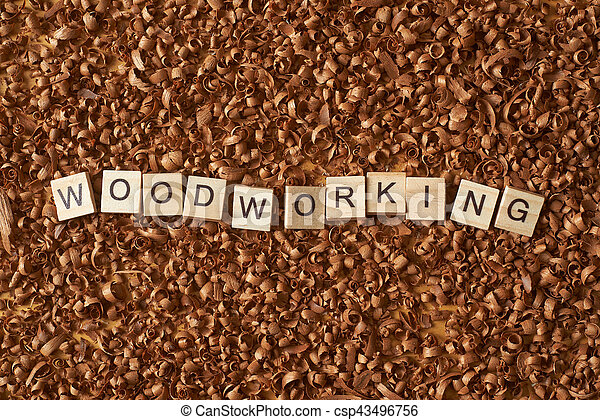 Woodworking word writen with letters on a wood chips - csp43496756