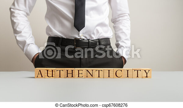 Word Authenticity spelled on desk with wooden cubes - csp67608276