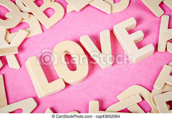 Word LOVE wooden on pink background. - csp43602064