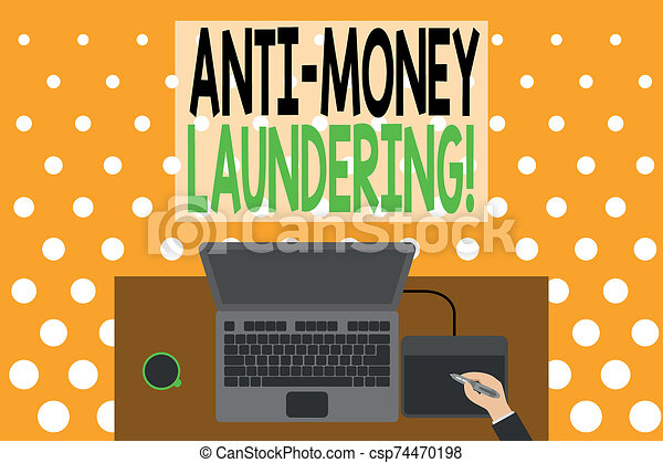 Word writing text Anti Money Laundering. Business concept for regulations stop generating income through illegal actions Upper view laptop wooden desk worker drawing tablet coffee cup office. - csp74470198