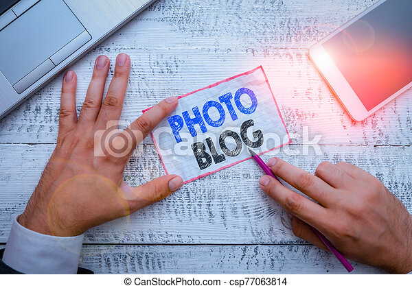 Word writing text Photo Blog. Business concept for form of photo sharing and publishing in the format of a blog Hand hold note paper near writing equipment and modern smartphone device. - csp77063814