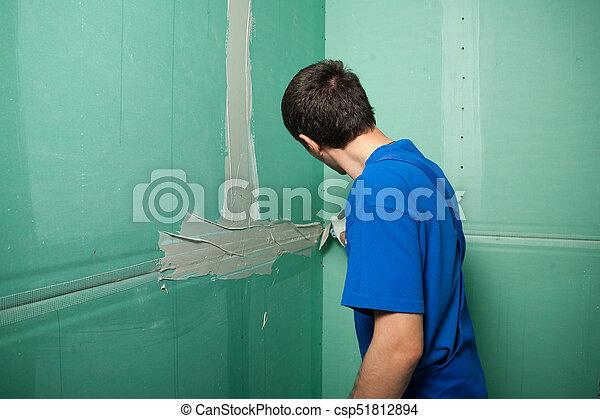 Manos de yeso en el trabajo. La solicitud del yeso en la pared - csp51812894