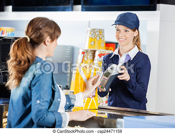 Worker Accepting Payment From Woman Through NFC Technology At Ci - csp24471159