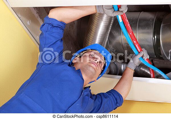 Worker holding blue and red pipes under air ducts - csp8611114