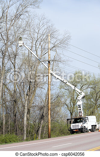 Worker in a lift truck, trimming trees beside power lines - csp6042056