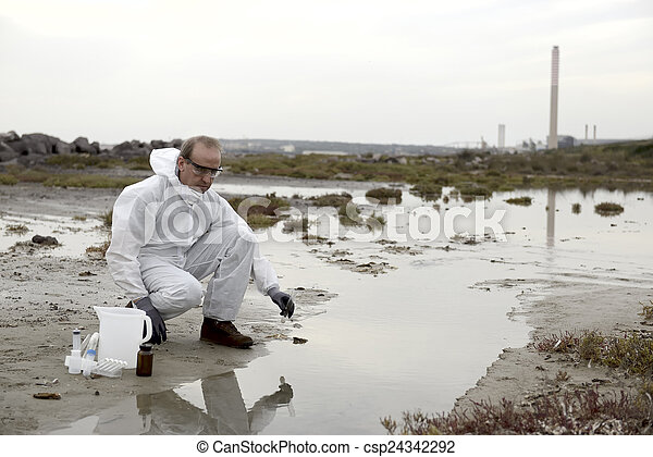 Worker in a protective suit examining pollution - csp24342292