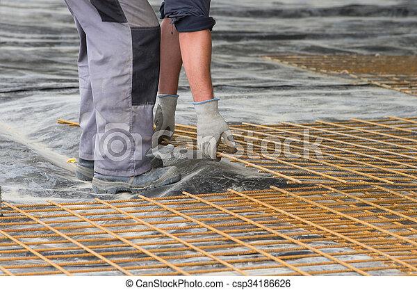 Worker installing reinforcement mesh - csp34186626