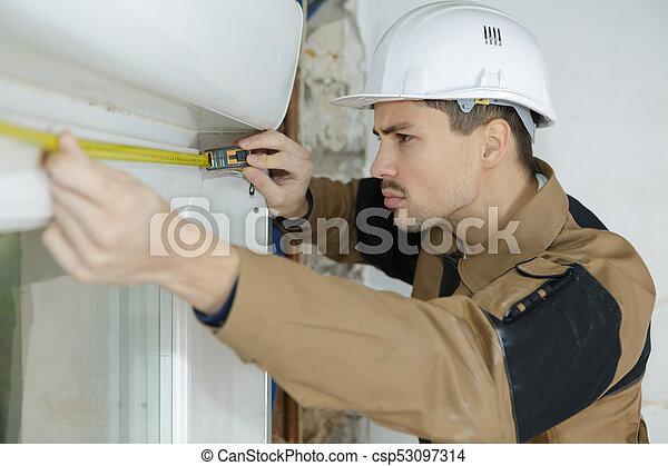 worker measuring the window - csp53097314