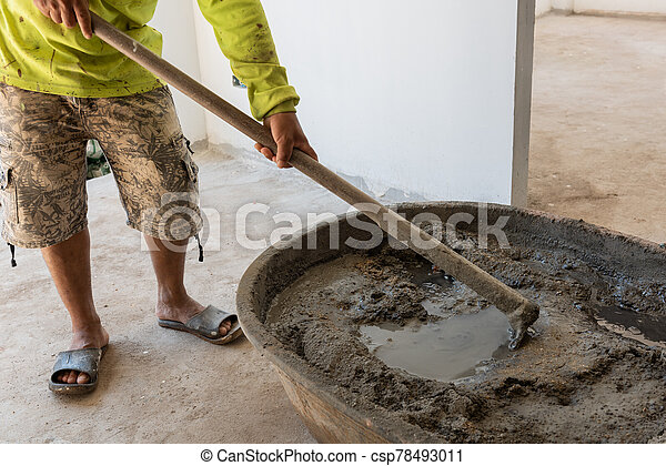 Worker mixing cement mortar at construction site - csp78493011
