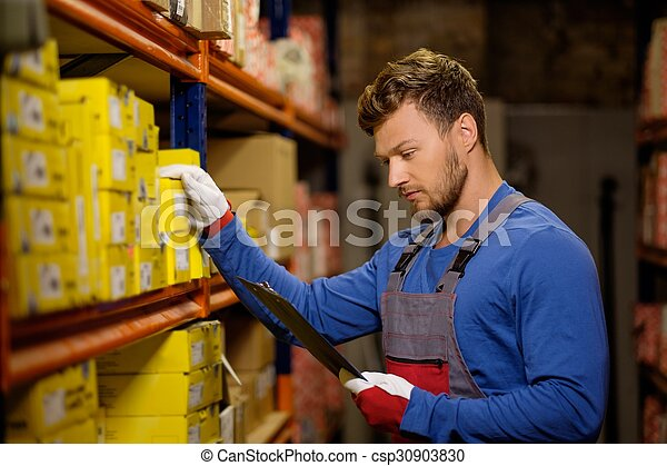 Worker on a automotive spare parts warehouse  - csp30903830